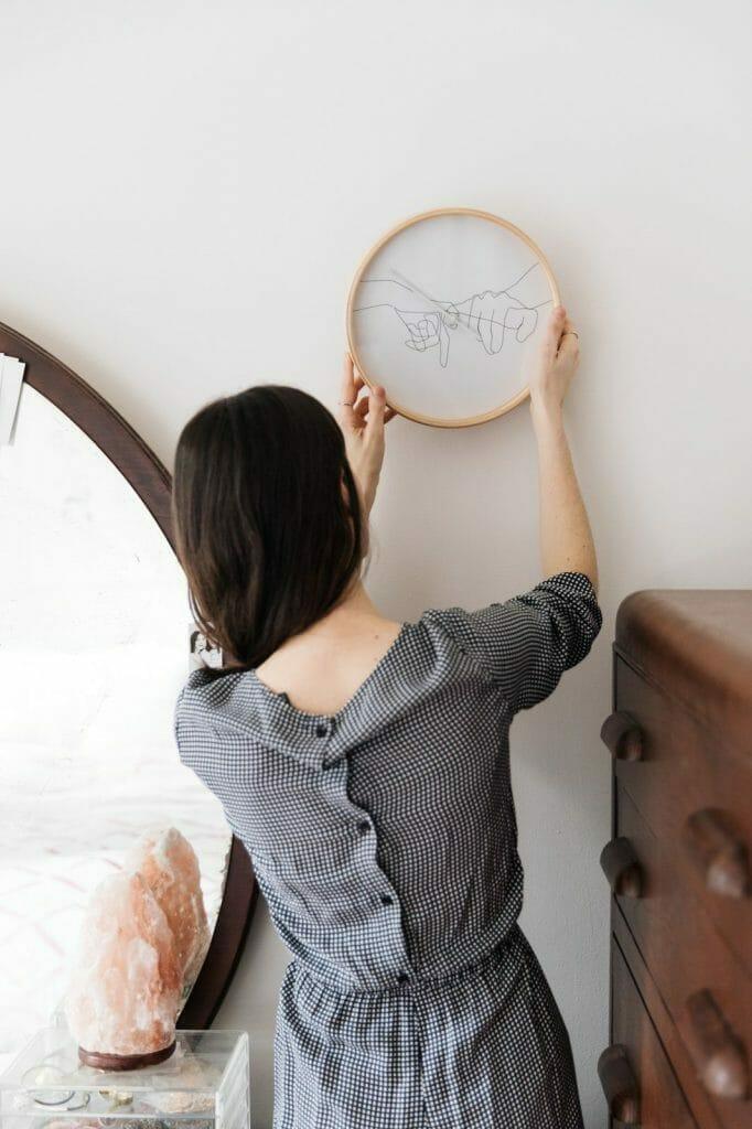 dziewczyna wieszająca haft na scianie