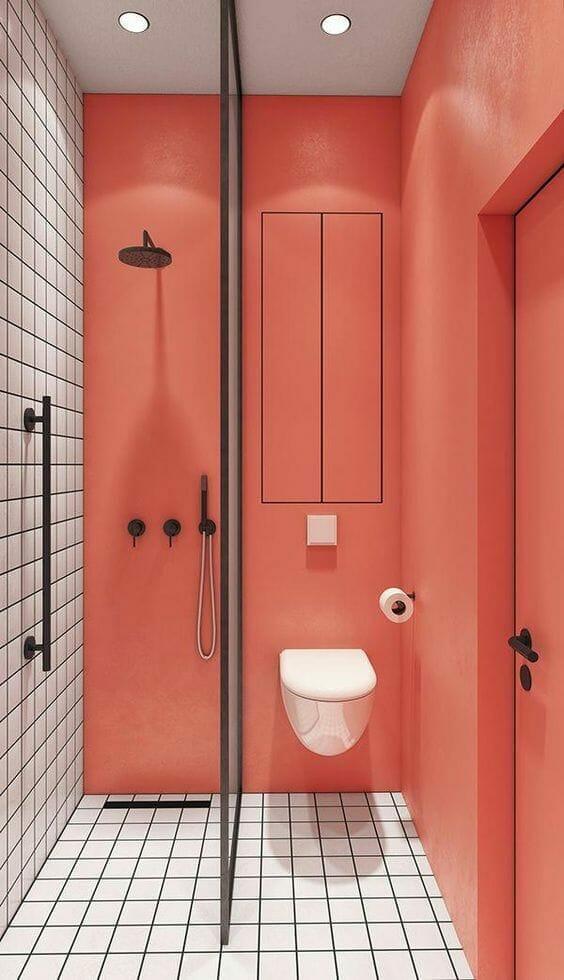 vonios kambarys su gyvomis koralų spalvomis su baltomis plytelėmis ir juodais aksesuarais baterijų pavidalu