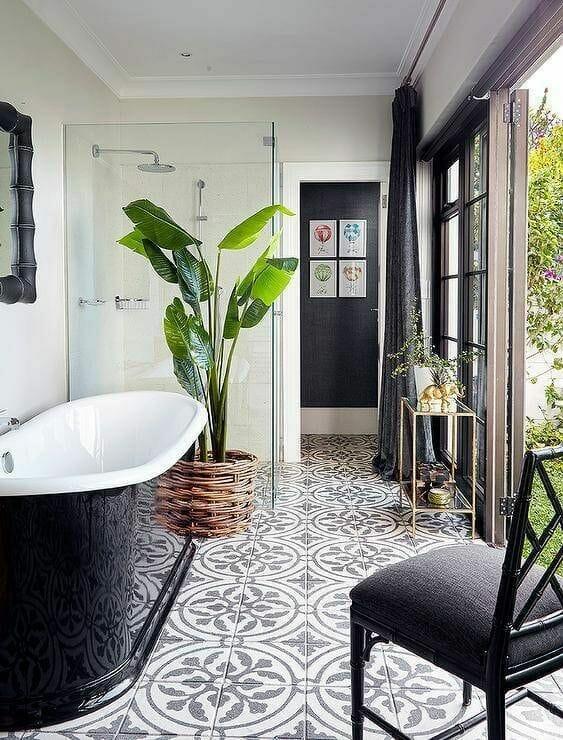 czarno biała łazienka z wanną wolnostojącą i rośliną tropikalną palma w łazience