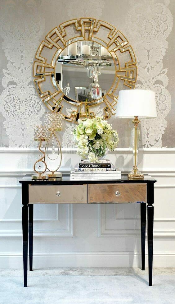 lustro styl glamour w złotej ramie na beżowej ścianie z tapetą