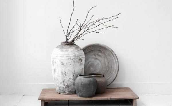 ceramika postarzana z gałązkami na białej ścianie