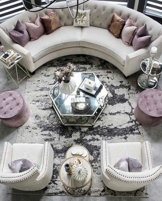 beżowy zestaw wypoczynkowy w salonie z różowymi poduszkami i pufami