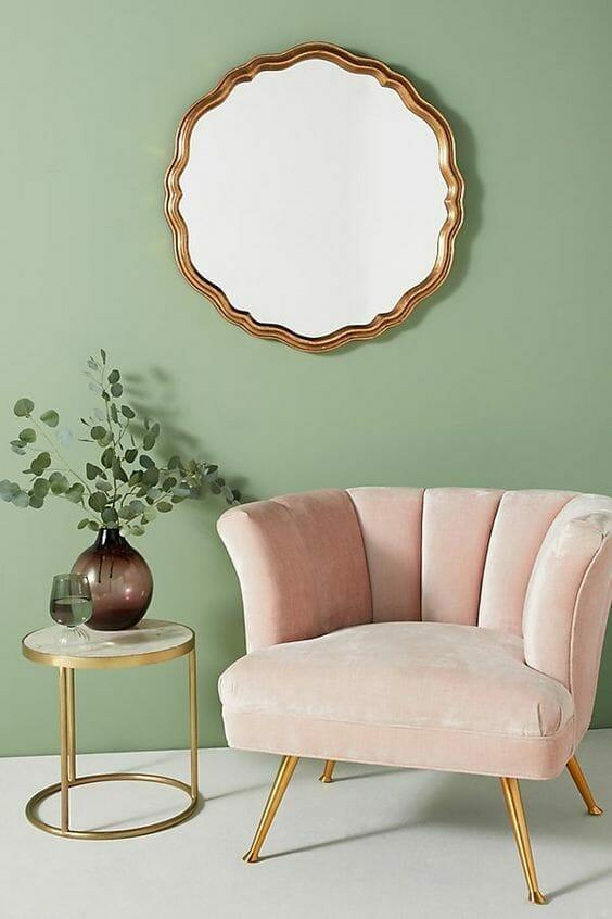 welurowe różowe krzesło ze stoliczkiem na tle seledynowej ściany