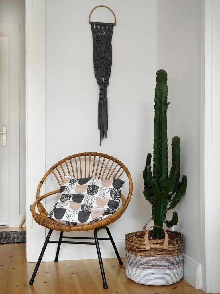 bambusowe krzesło w stylu urban jungle szara makrama na ścianie i duży kaktus w doniczce