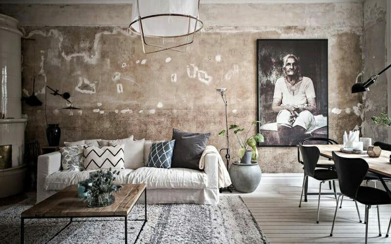 salon w stylu wabi-sabi z odrapanymi ścianami, beżową kanapą z poduszkami i obrazem starszej kobiety