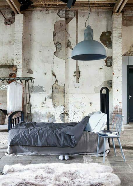 sypialnia z odrapanymi ścianami i futrzanym dywanem, szarą lampą sufitową i pościelą styl wabi-sabi