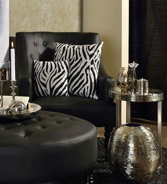 czarny, pikowany skórzany fotel i pufa, z przodu dopasowany stolik i wazon w srebrnym kolorze