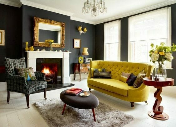 salon w stylu glamour z czarnymi ścianami, jasną podłogą i kontrastującą musztardową sofą, nad kominkiem wisi lustro w złotej barokowej ramie, z sufitu zwisa dekoracyjny żyrandol