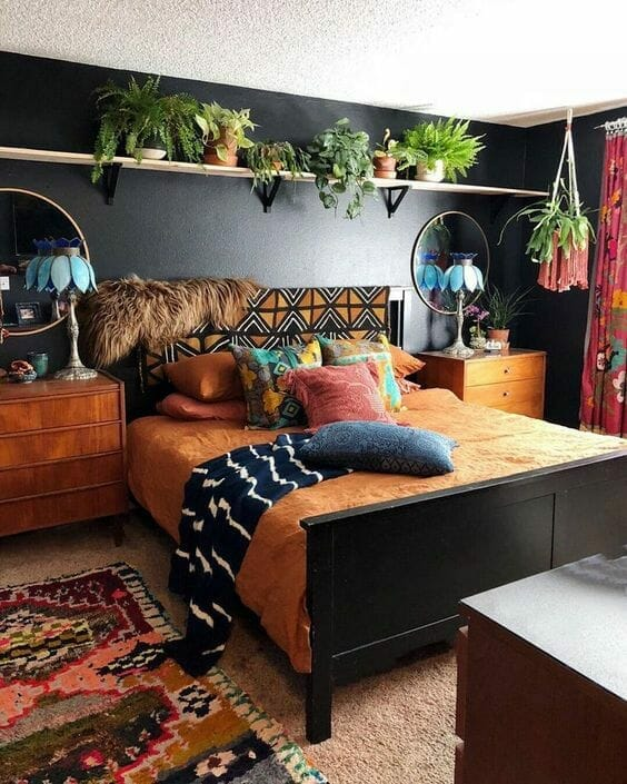 sypialnia urban jungle z dodatkami boho niebieskie klosze lamp vinatge etniczne wzory na tekstyliach czarne ściany i brązowa narzuta