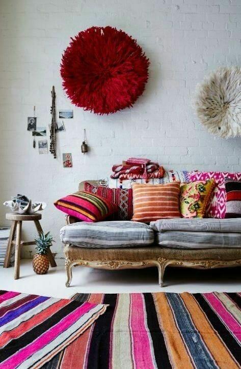 kolorowy salon z barokową sofą i poduszki w etniczne wzory dywan w kolorowe pasy