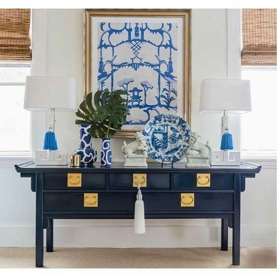 styl chinoiserie - granatowa komoda ze złotymi zdobieniami, białe lampy i porcelanowe wazony i talerz