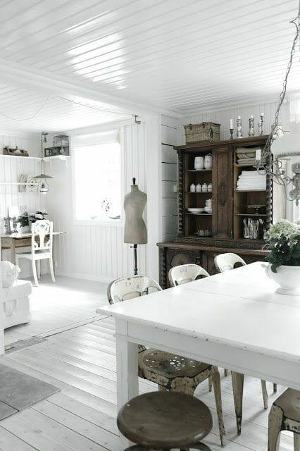 salon z białymi deskami na ścianach, stołem i krzesłami i ciemnym, starym kredensem trendy 2019