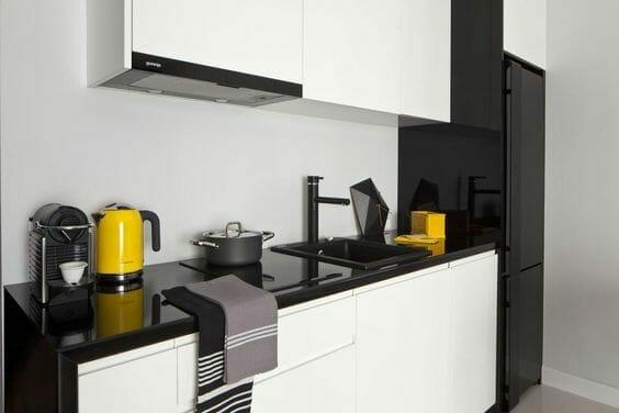 kuchnia w stylu skandynawskim w kolorze czerni i bieli z żółtymi dodatkami w postaci czajnika i pudełka