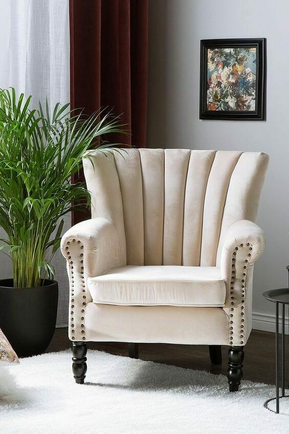 elegancki welurowy fotel typu uszak w styl glamour w kolorze kremowym, w tle palma areka i welurowe zasłony