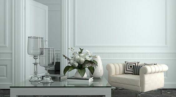 na pierwszym planie stolik ze szklanym blatem, wazony i kwiaty, w tle niewielki niski pikowany fotel w kolorze kremowym oraz biała ściana w dekoracyjną boazerie