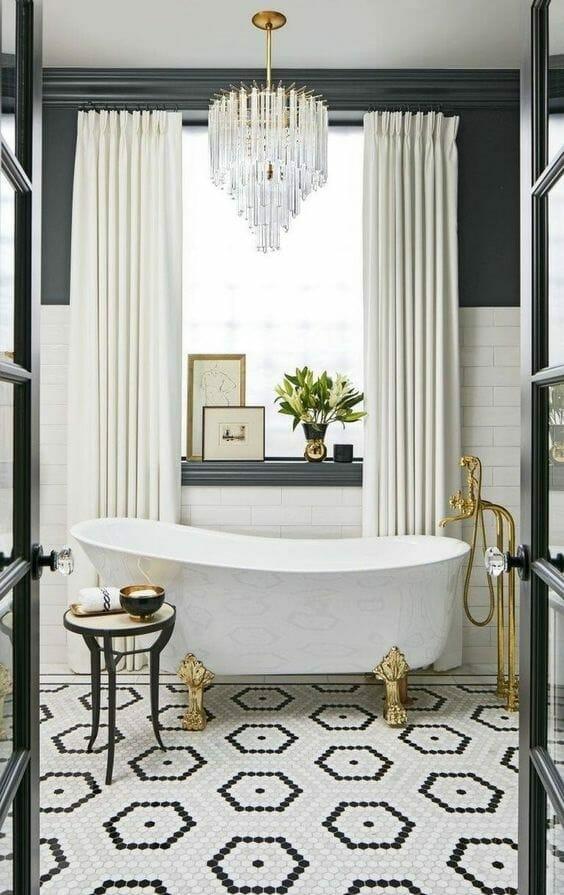 łazienka z mozaiką na podłodze białą wanną na nóżkach i złotą baterią, kryształowy żyrandol