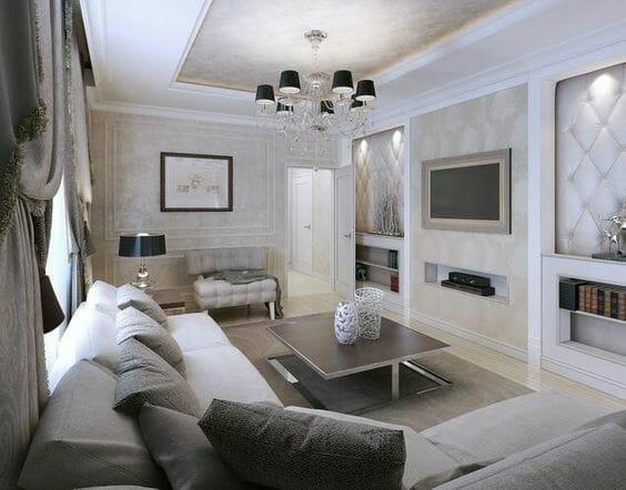 przestronny salon w styl glamour z dużym żyrandolem i pikowanymi ścianami, szara sofa