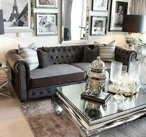 salon z ciemnoszarą kanapą i srebrnym stolikiem kawowym i kryształową zastawą