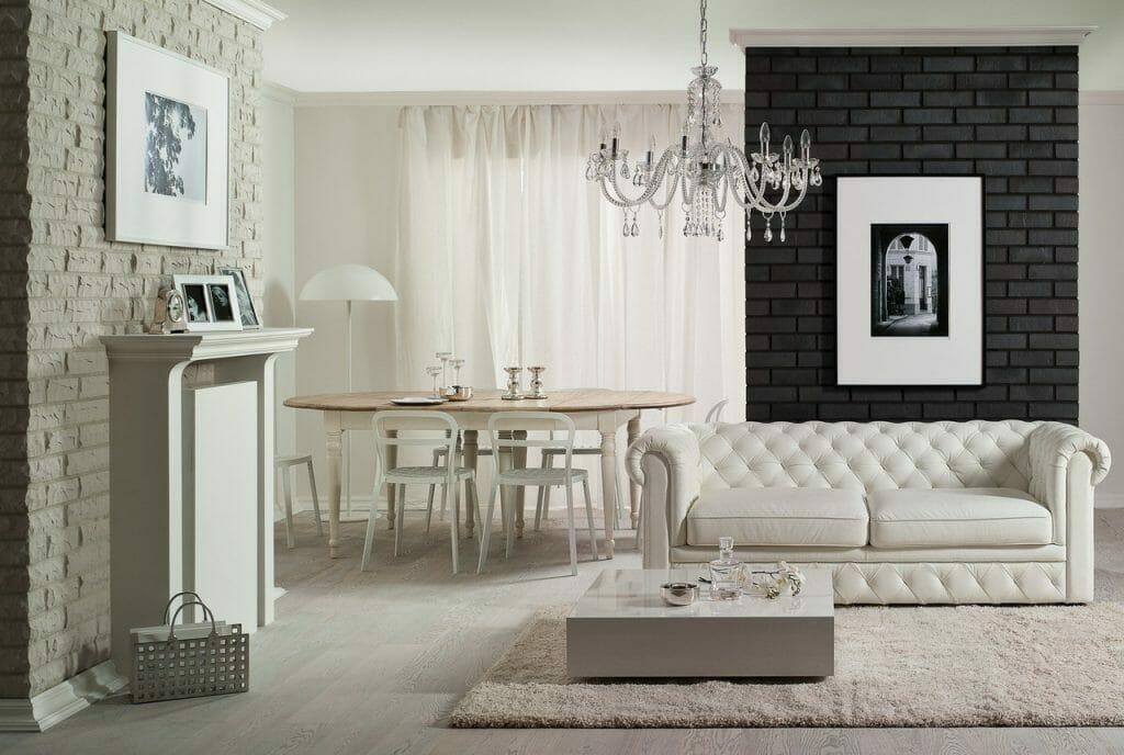czarno biały salon z żyrandolem i nagą cegłą, w tle stół jadalniany z białymi krzesłami, kanapa i kominek na pierwszym planie