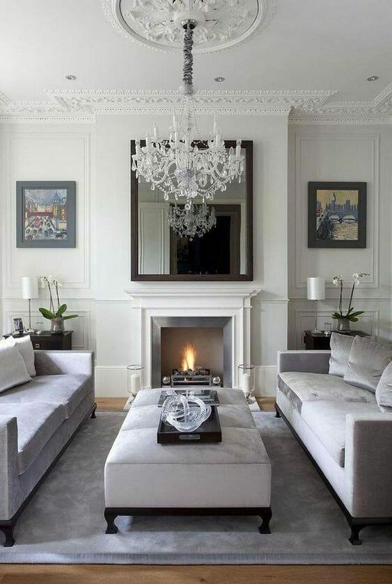 salon glamour z białymi ścianami z dekorami, kominkiem, kryształowym żyrandolem i welurowymi sofami