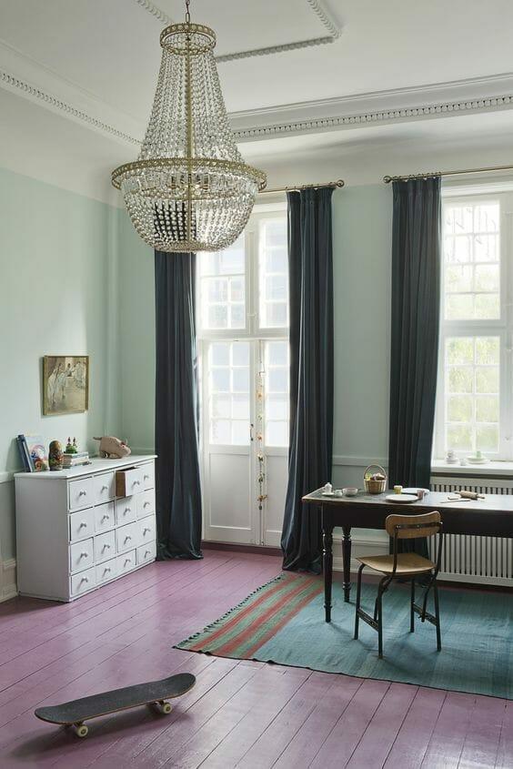 pokój turkusowy z kryształowym żyrandolem i różową podłogą z deskorolką i biurkiem