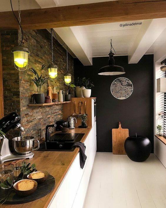 czarno biała kuchnia z ceglastą ścianą i drewnianym blatem i czarnym zlewem z baterią z dużą ilością roślin