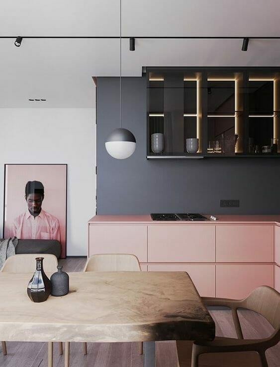 kuchnia w stylu skandynawskim w kolorze różu i grafitu z półkami oświetlonymi ledami i drewnianym stołem