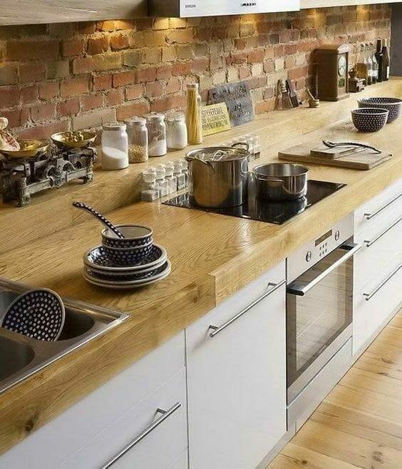 kuchnia z ceglaną ścianą i wysuwanymi szafkami