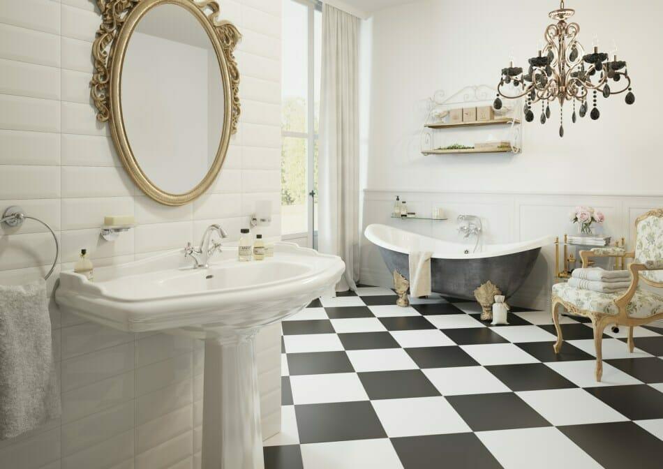 łazienka glamour z czarno-białymi kafelkami, czarnym żyrandolem, wanną wolnostojącą i lustrem ze złotą ramą