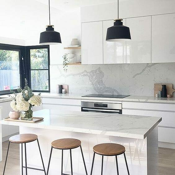 biała kuchnia z wyspą i trzema stołkami barowymi z drewnianym siedzeniem, marmurowe blaty