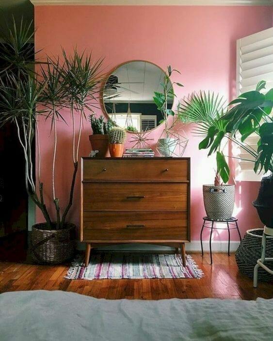 różowa ściana w sypialni z dużą ilością roślin
