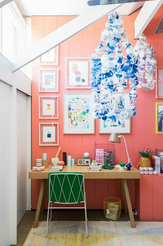 biuro w kolorze living coral z kolorowymi dodatkami, zielonym krzesłem i kolorowymi obrazkami