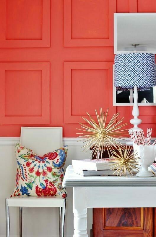living coral na ścianach z beżowym krzesłem i białym stołem ze złotymi dodatkami