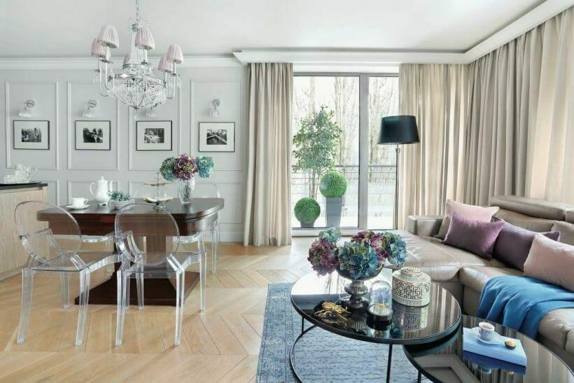 przestronny salon połączony z jadalnią, jasny parkiet w jodełkę, białe ściany z dekorami i galerią zdjęć, stolik kawowy z kwiatami
