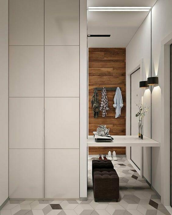 nowoczesny szary przedpokój z białą szafą siedziskiem i lustrem drewniana ściana