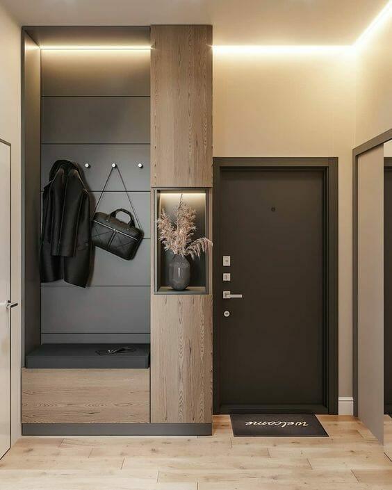 nowoczesny przedpokój w kolorze beżu i szarości czarne drzwi zabudowa ściany meble do przedpokoju dodatki do przedpokoju w postaci szarego wazonu z zasuszonymi liśćmi