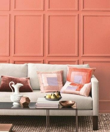 koralų spalva ant sienos su smėlio spalvos sofa ir rausvomis pagalvėlėmis