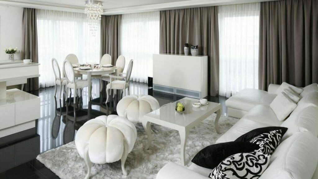 Biało czarny przestronny salon, biała kanapa, stolik kawowy i pufy, czarna podłoga z płytek, kremowe zasłony