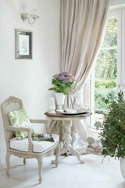 krzesło i stolik w stylu shabby chic, w jasnym pomieszczeniu o kremowej kolorystyce. Z okna w prawym roku rozpościera się widok na ogród