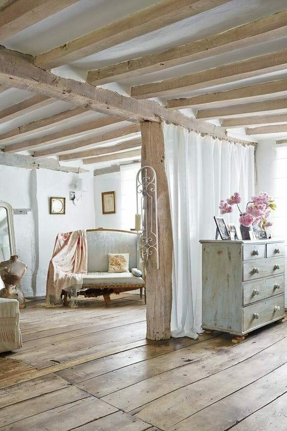rustykalne wnętrze z drewnianymi belkami dachowymi i parkietem, postarzana komoda i barokowa sofa shabby chic