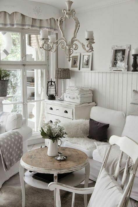 Pokój wypoczynkowy w stylu shabby chic z białą boazerią na ścianie, stolikiem kawowym i białą kanapą