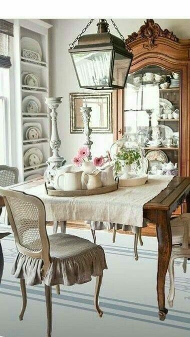 jadalnia w stylu shabby chic, drewniany stół nakryty lnianym obrusem, w tle ciężki drewniany kredens z porcelaną. Jasne pomieszczenie z kremowymi ścianami
