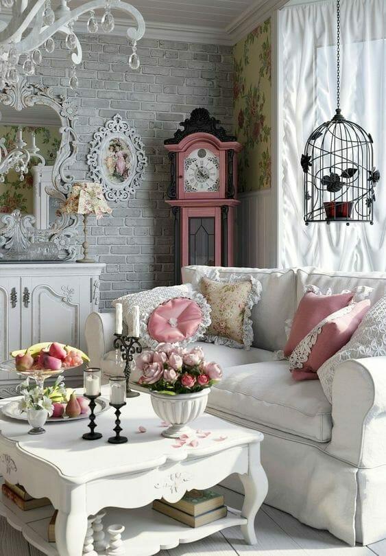 salon w stylu rustykalnym, z szarą cegłą na ścianie i dekoracyjną sofą, różowy zegar stojący