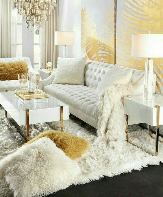 biały salon glamour ze złotymi akcentami, na ścianie fototapeta w złote liście paproci, przed białą sofą stoją geometryczne stoliki ze złotymi nogami, na podłodze leży kremowy dywan typu shabby