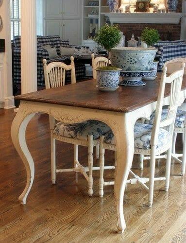 styl toskańśki biały masywny stół z ornamentami i krzesła z niebieskim obszyciem