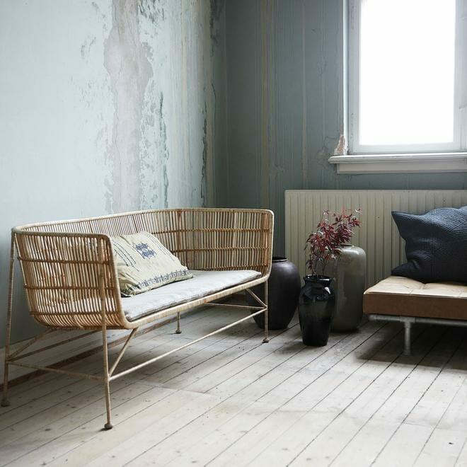 wnętrze wabi-sabi z wiklinową kanapą i odrapanymi ścianami