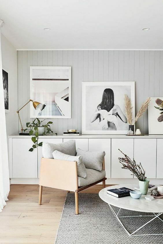 salon z szarymi deskami na ścianie i białymi zdjęciami na ścianie