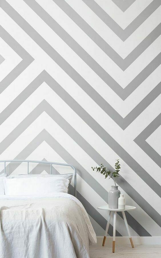 łóżko na tle szaro-białej tapety w pasy