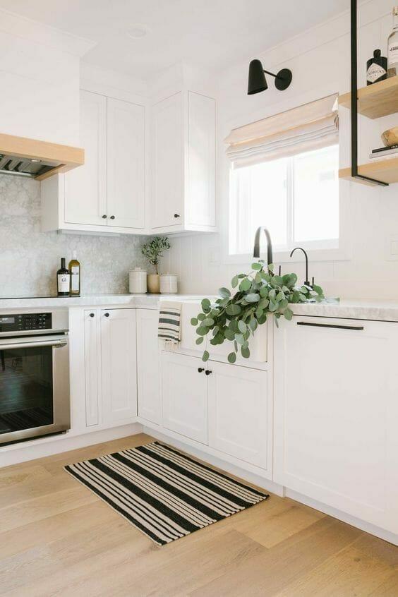 biała minimalistyczna kuchnia z marmurowym blatem i drewnianymi półkami i chodniczkiem w paski