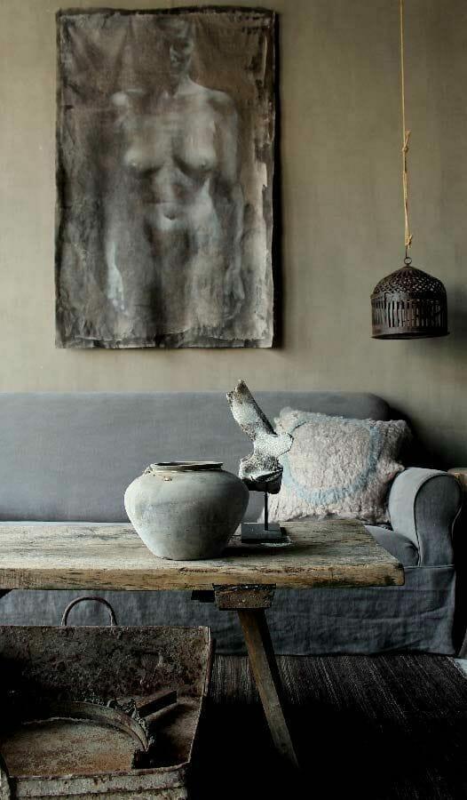 salon w stylu wabi-sabi z starym stołem i szarą kanapą i postrzępionym obrazem nagiej kobiety